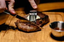 Male's hands begin to cut steak using knife and fork